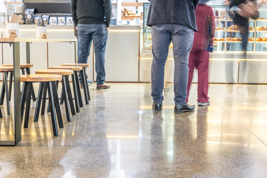 people standing on polished concrete floor in cafe