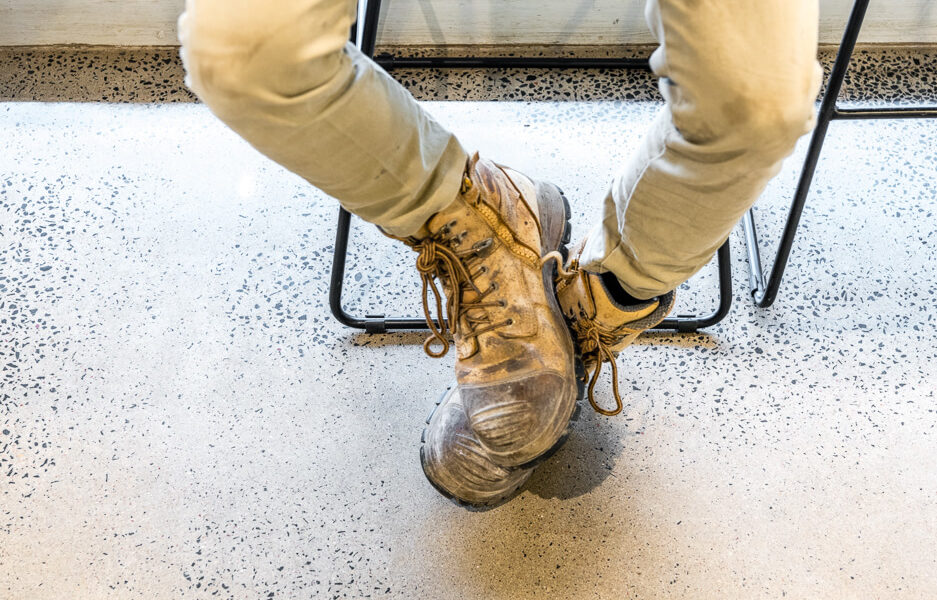 Person's legs wearing reinforced work boots