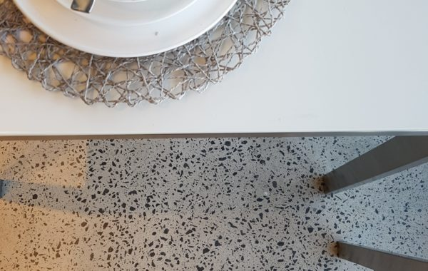 white table with black legs on concrete flooring