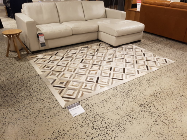 couch and rug on concrete floor