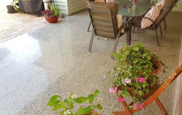 outdoor dining table on concrete floor with pot plants