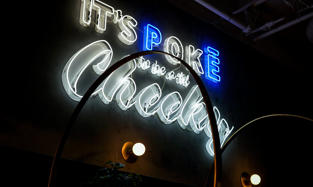Neon sign showing Cheeky Poke's slogan
