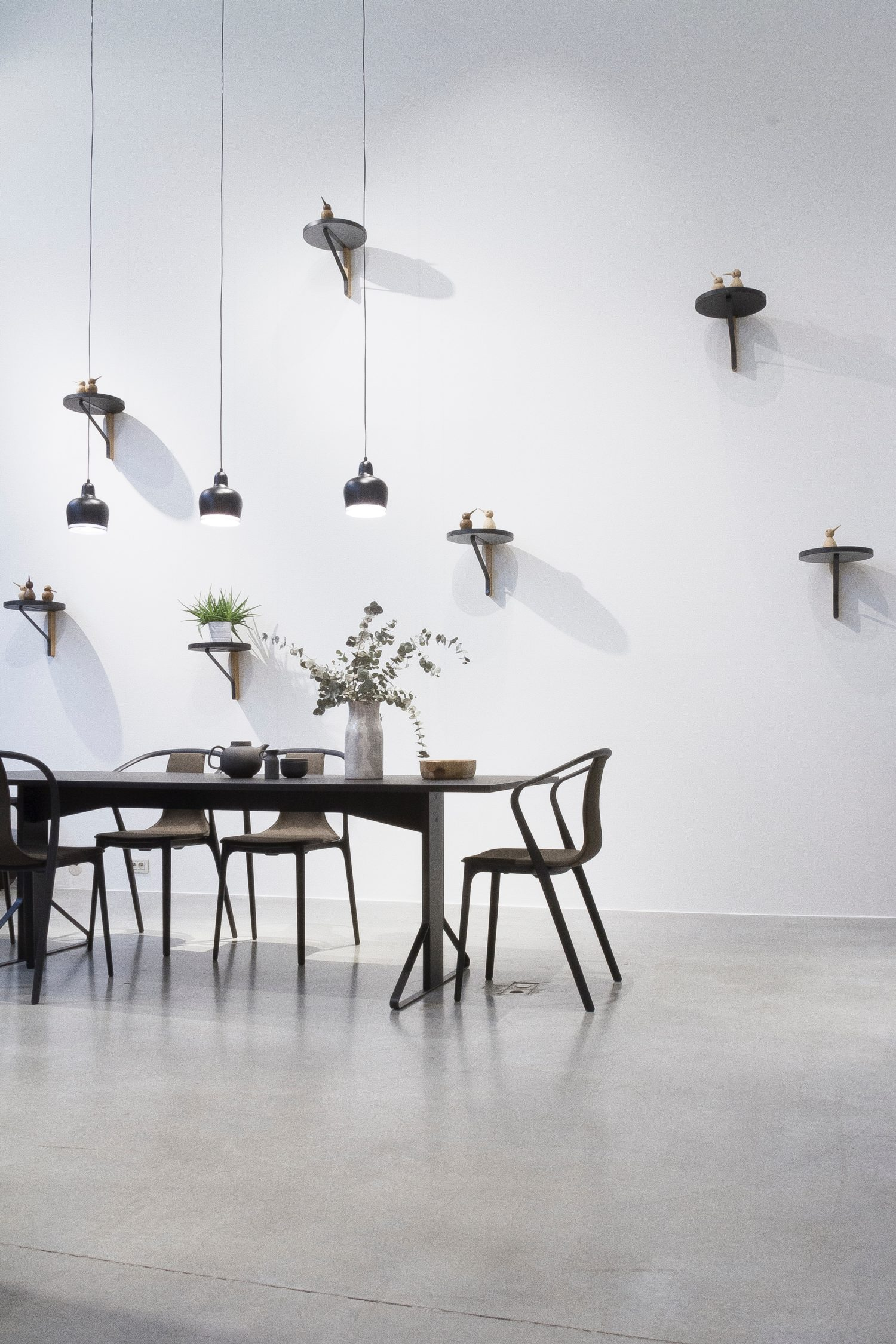 small dining table on concrete floor and hanging lights